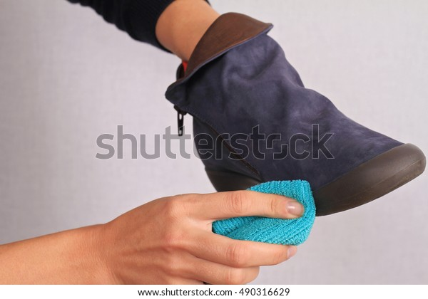 Woman cleaning Chamois Leather Shoes. Suede shoes winter care