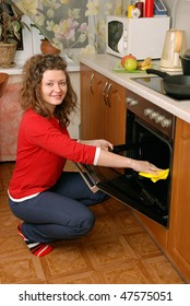 woman cleaning contemporary kitchen oven