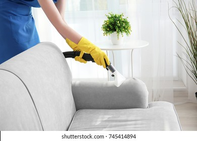 Woman cleaning couch with vacuum cleaner at home