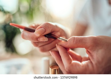 Woman cleaning cuticles with cuticle pusher