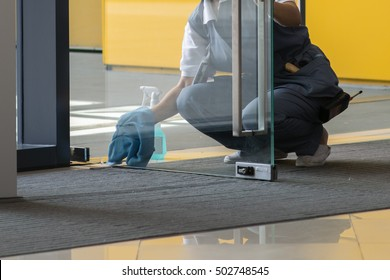 A woman cleaning the door.