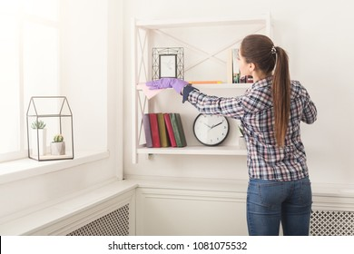 Woman cleaning dust from bookshelf. Young girl sweeping shelf, spring cleaning concept, copy space