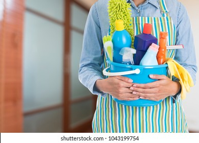 woman with cleaning equipment ready to clean house in the room background