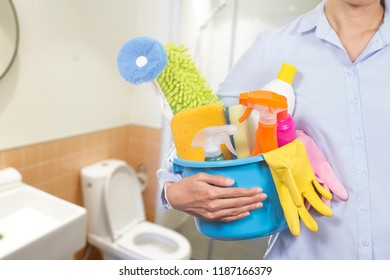 woman with cleaning equipment ready to clean bathroom