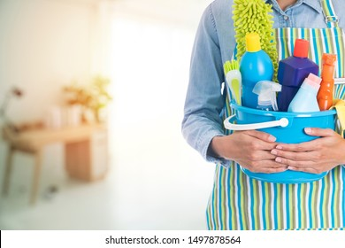 woman with cleaning equipment ready to clean house on living room blur background