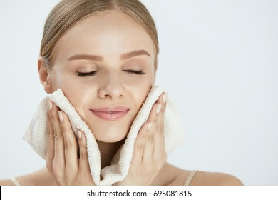 Woman Cleaning Face With White Towel. Closeup Portrait Of Beautiful Happy Smiling Young Female Wiping Facial Skin With Soft Facial Towel After Washing Face. High Resolution