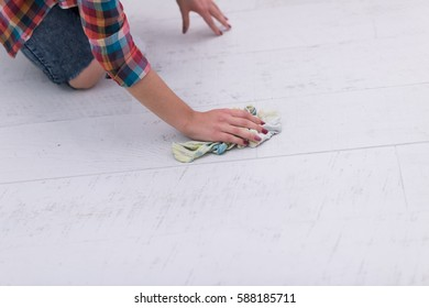 woman cleaning the floor at home with a focus on hands