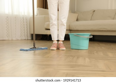 Woman cleaning floor with mop at home, closeup