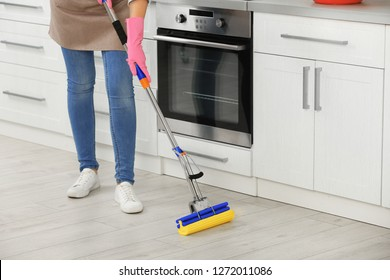 Woman cleaning floor with mop in kitchen