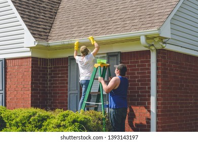 Woman Cleaning Gutters While Standing On Ladder