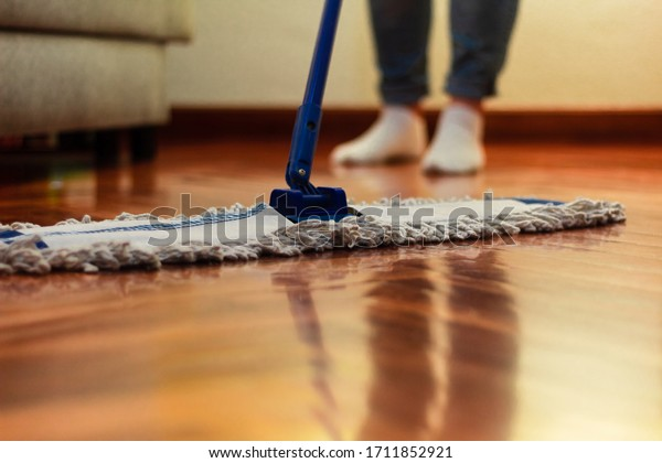 A woman cleaning the hardwood floor, with a close-up of the mop and a blurred background of feet and a sofa. hardwood floor cleaning
