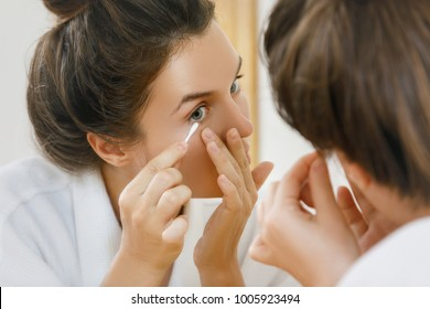 Woman cleaning her eye with a cotton swab