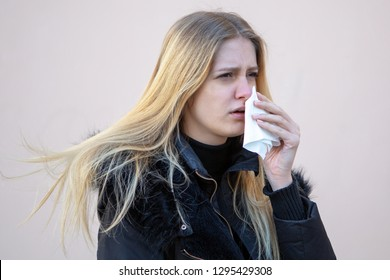 Woman cleaning her nose in winter
