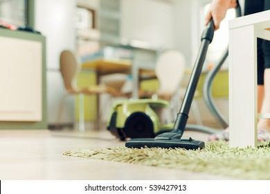 Woman cleaning home with vacuum cleaner.