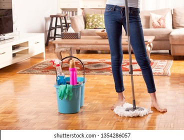 woman cleaning house with detergents