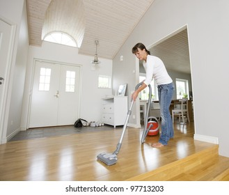 Woman cleaning the house with the Vacuum Cleaner