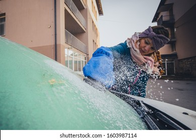Woman is cleaning an icy window on a car with ice scraper designed as a glove. Ice and snow chunks flying from the scraper. Cold snowy and frosty morning.