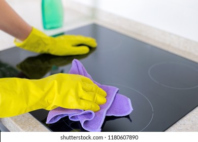 Woman cleaning induction top, hand in yellow rubber glove polish stove cooktop, closeup, no face. Concept of clear kitchen appliance