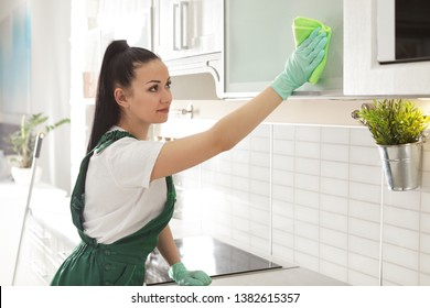 Woman cleaning kitchen cabinet with rag indoors