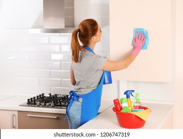Woman cleaning kitchen with rag, indoors