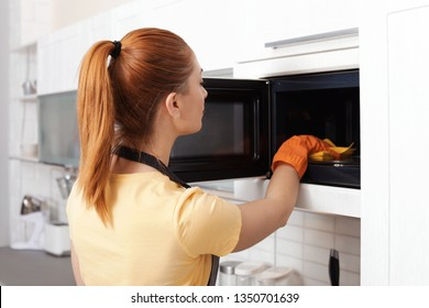 Woman cleaning microwave oven with rag in kitchen