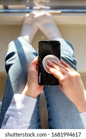 Woman cleaning mobile phone to eliminate germs, coronavirus, covid-19, bacterias. Female disinfects a smartphone by applying sanitizer/alcohol disinfecting foam using a cotton pad, close up. Top view.