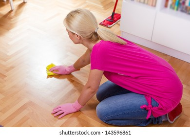 Woman cleaning and mopping floor at home.