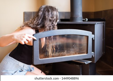 Woman cleaning opening rustic vintage country home fireplace in cottage cabin during summer