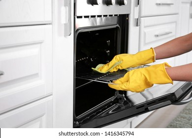 Woman cleaning oven in kitchen