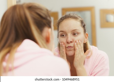 Woman cleaning peeling her face in bathroom, making facial massage with scrub. Girl taking care of skin condition. Hygiene. Skincare spa treatment.