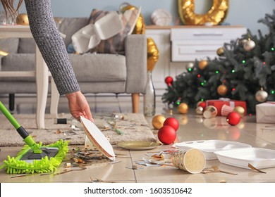Woman cleaning up room after New Year party