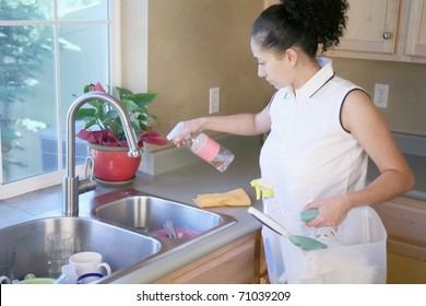 Woman cleaning the sink in a kitchen spraying the sink and counter top