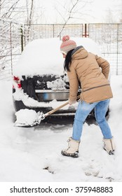 Woman cleaning snow around car and making a path