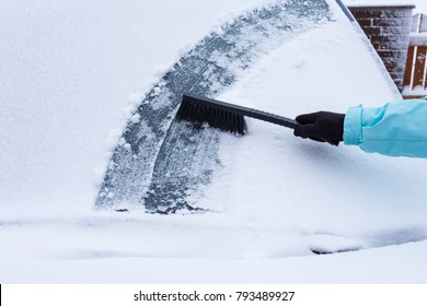 Woman cleaning snow from the car in the winter