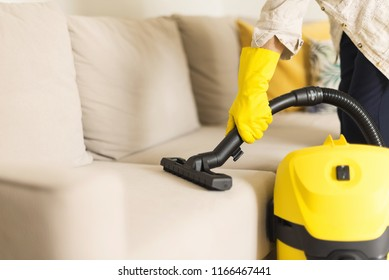 Woman cleaning sofa with yellow vacuum cleaner. Copy space. Clean concept.