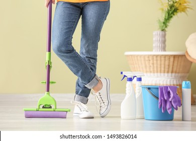 Woman with cleaning supplies in room