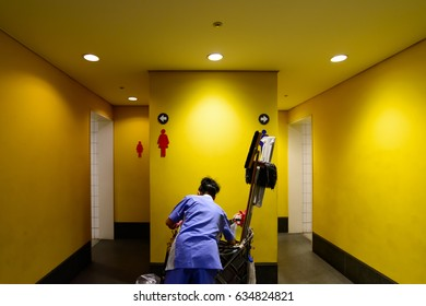 A woman cleaning a toilet in a shopping mall.