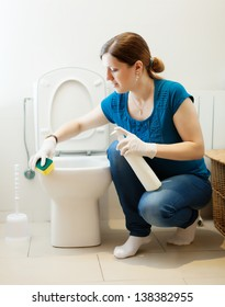 Woman cleaning toilet with sponge and cleaner at  home