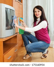 woman cleaning TV with cleanser at home
