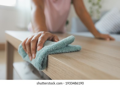 Woman cleaning and wiping the table with microfiber cloth in the living room. Woman doing chores at home. Housekeeping concept.
