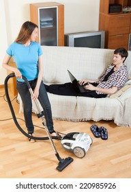 Woman cleaningwith vaccuumcleaner at home while young man with notebook resting over sofa