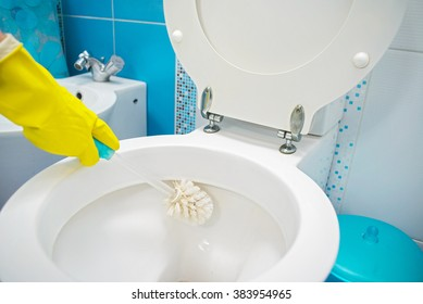 A woman cleans a bathroom toilet with a scrub brush.