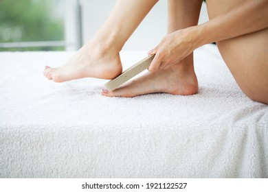 Woman cleans the heel of the foot with pumice