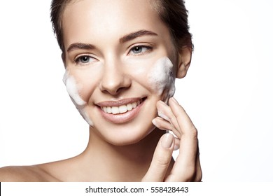 Woman cleanses  the skin foam on a white background isolated