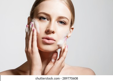 Woman clears a face skin foam on a gray background