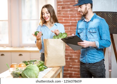 Woman client cheking products standing with delivery worker on the kitchen at home