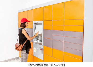 Woman client using automated self service post terminal machine or locker to receive a parcel or to deposit the luggage for storage