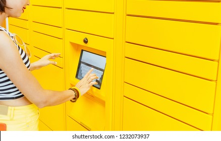 Woman client using automated self service post terminal machine or locker to deposit the parcel for storage,