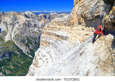 "Woman climber ascending along the steel cable of via ferrata ""Lipella"", Tofana massif, Dolomite Alps, Italy"