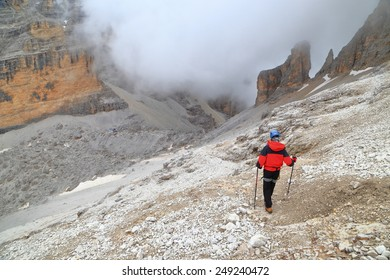 Woman climber descending towards cloud covered valley and Pomedes refuge, Tofana massif, Dolomite Alps, Italy